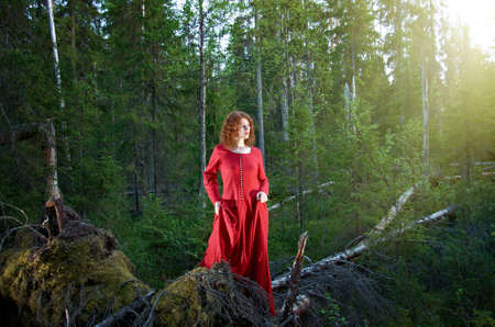 priestess: Young woman in red dress in the mystical forest. Stock Photo