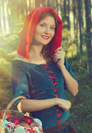 caperucita roja: caperucita roja na bosque denso. hermosa chica en traje medieval