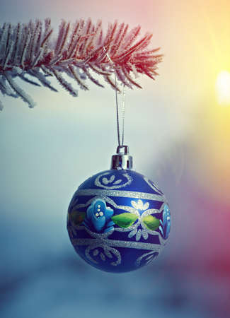 christmas tree branch: bright Christmas bauble from a snow covered Christmas Tree Branch Stock Photo