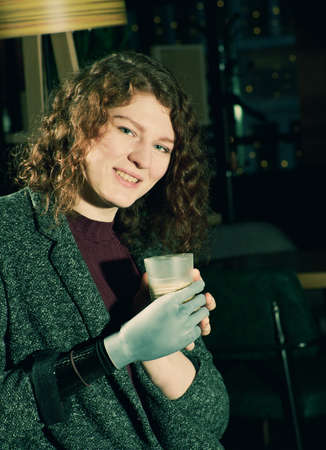 Young woman with prosthetic arm drinks cofee Stock Photo