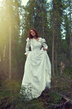Young woman in white long dress in the mystical forest.