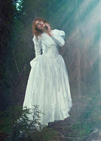 rite: Young woman in white long dress in the mystical forest.