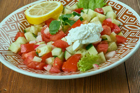 israeli: Choban salatasi - Shepherds Salad, Turkish salad consisting of finely chopped tomatoes , cucumbers, long green peppers, onion, and flat-leaf parsley. Stock Photo
