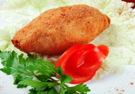 Chicken Kiev -  dish of chicken fillet pounded and rolled around cold butter, then coated with eggs and bread crumbs, and either fried or baked.Boneless version