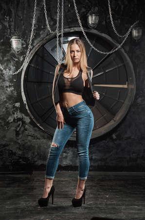 beautiful sexy brunette girl on the grunge industrial ventilator Standard-Bild
