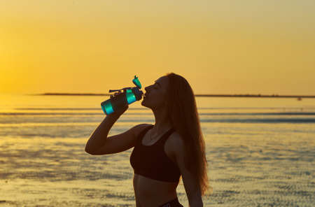 Silhouette  beautiful girl with sports on the beach drinking water from a sports bottle 版權商用圖片