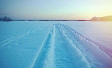 Winter landscape.trace of a snowmobile on frozen lake