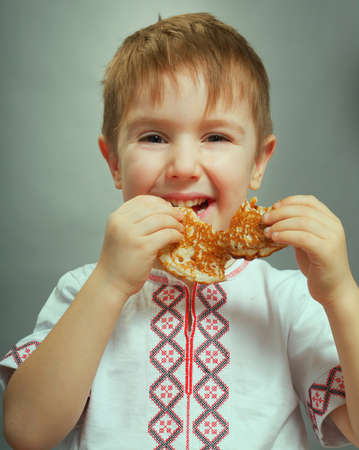 Russian little boy eats pancakes with red caviar.