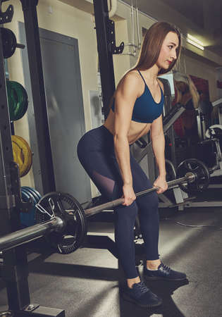 sporty woman builds muscle arms and chest on the simulator in the gym.Girl doing exercises on a simulator in the gym 版權商用圖片