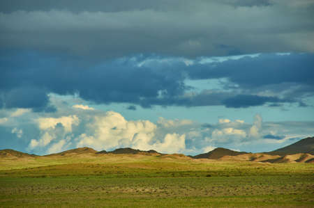 Mongolia. Sands Mongol Els dunes . Herds graze in the spring green valley
