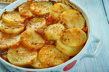 Tumbet - traditional vegetable dish from Majorca,  combines layers of sliced potatoes, aubergines and red bell peppers