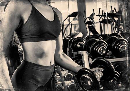 sportliche Frau baut Muskelarme und Brust auf dem Simulator im Fitnessstudio auf. Schönes Mädchen, das Übungen macht, Hanteln im Fitnessstudio hält Standard-Bild