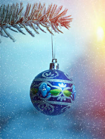 bright Christmas bauble from a snow covered Christmas Tree Branch Stock Photo
