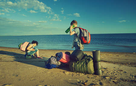 Boys use smartphones to communicate.  Crash on the coast of a deserted sea