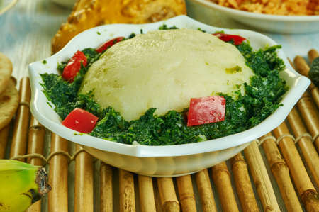 Ugali Sukuma Wiki, made with collard greens, known as sukuma, cooked with onions and spices. Kenyan cuisine, Traditional assorted African dishes, Top view. Stock Photo