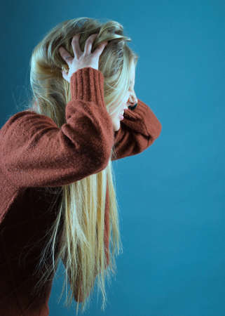 Young blond girl furiously scratches her tangled hair  on  gray background