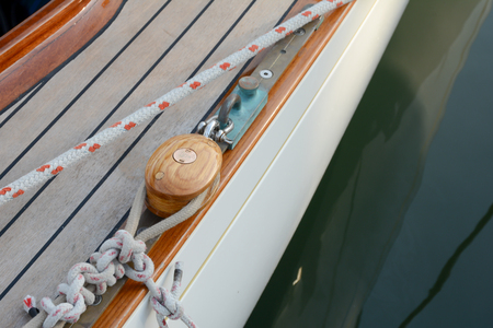 mooring bollards: Close-up ,nautical knot rope tied around stake on boat, boat mooring rope.