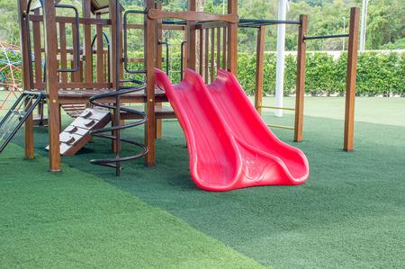 Slider (Kids speeltuin) in het park met kunstgras Stockfoto