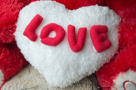 Red love  text  on teddy bear for Valentines Day with white heart  on wooden floor