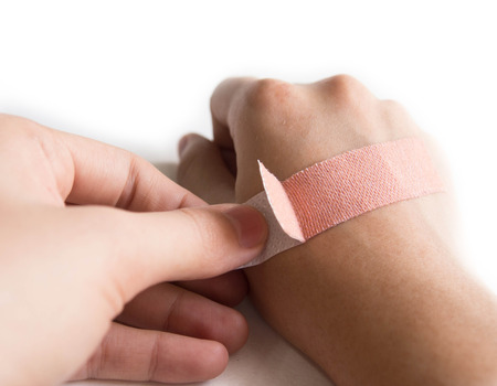 sticking to: Sticking hand with an adhesive plaster on isolated whited background Stock Photo