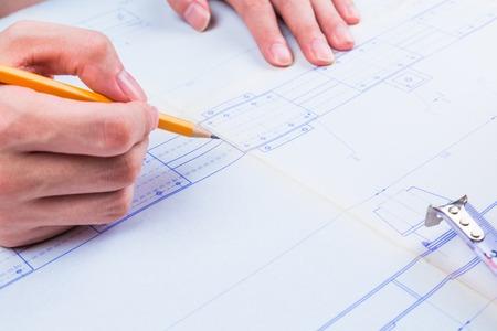 コンパスでの男の手。機械技師の仕事。技術的な図面。鉛筆、コンパス、電卓、手マン。技術的な図面と図の紙。 写真素材