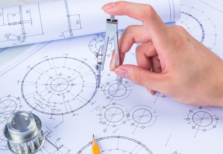 Man's hand with a compass. Mechanical engineer at work. Technical drawings. Pencil, compass, calculator and hand man. Paper with technical drawings and diagrams. Banque d'images
