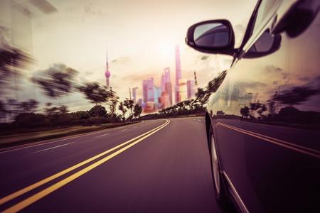 黒い車の運転の田舎道の側面図です。