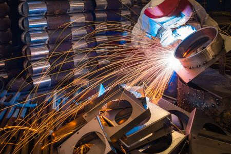 working man: sparks while welder uses torch to welding