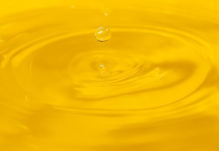 een druppel water valt in een gouden water. macro