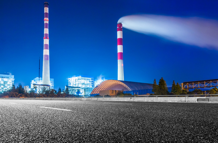 Factory With Smoke Stack Against Sky At Night.