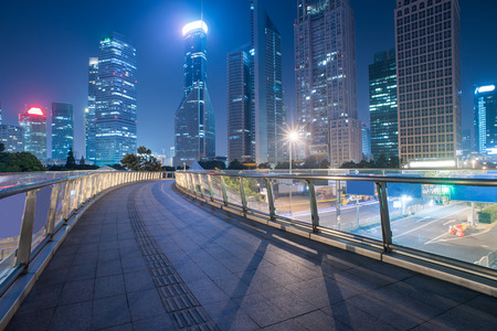 中国・上海に夜の街並みと歩道橋。