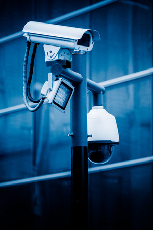 cctv security camera against building in blue tone stock photo