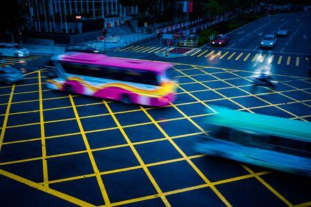 quadratic: cars driving through yellow no parking area on asphalt street,blue toned,china. Stock Photo