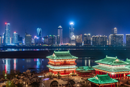 buildings standing by riverside under dramatic sky in Nanchang,China.