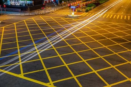 quadratic: cars driving through yellow no parking area on asphalt street.