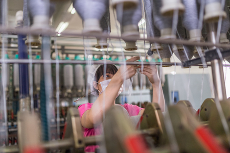 female worker standing beside thread making machine inside cotton mill,industry concepts. Reklamní fotografie - 80485369