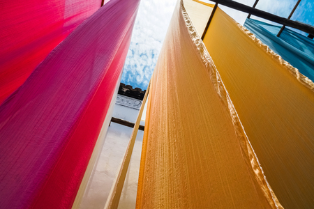 colorful fabric hanging to dry after traditional dye process,shot in Heng Dian Town,Zhejiang province of China. 版權商用圖片 - 80453898