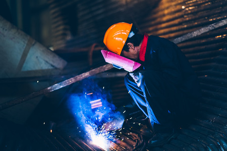 Worker doing electric welding,factory manufacturing,industry concepts. Stock Photo