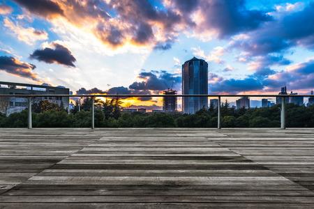 empty wooden platform with Shanghai skyline at twilight in background.