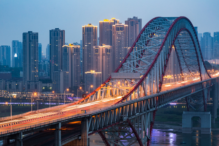 Long bridge across river at night in city of China. Banco de Imagens