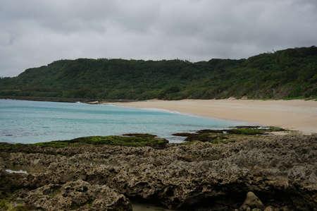 seawater: dark brown reef and yellow beach and green seawater and hill,taiwan,Kendin Stock Photo