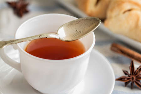 teaspoon: white china cup of black tea with teaspoon cubic sugar and fresh baked pastry Stock Photo