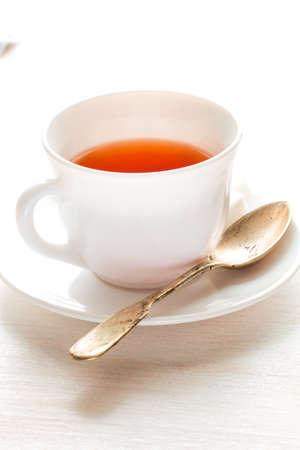 teaspoon: white china cup on  of black tea with silver teaspoon