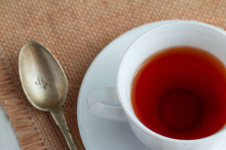 teaspoon: white china cup of black tea with teaspoon and cubic sugar  on canvas tablecloth Stock Photo