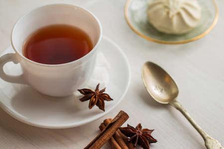 teaspoon: cup of tea with teaspoon, anise and marshmellow on saucer Stock Photo