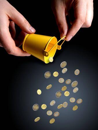 bucket of money: Bucket in hands and coins. Business concept.