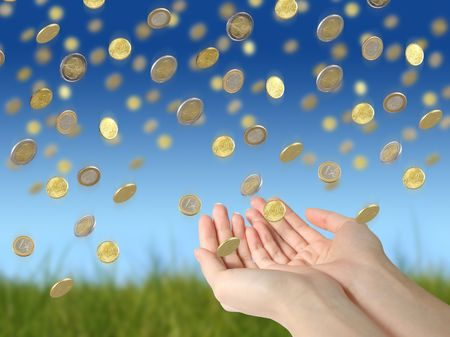 Coins falling to hands over blue sky background.  Stock Photo
