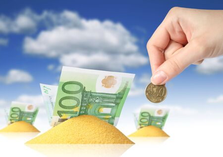Financial concept. Hand, sand and money over blue sky background.