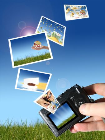Camera and a lot of pictures. Sky and grass on the background. Stock Photo