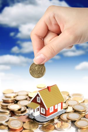 Invest in real estate concept. Hand and house on sky background. photo